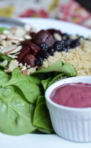 A side of blueberry vinaigrette with a spinach and beet salad.