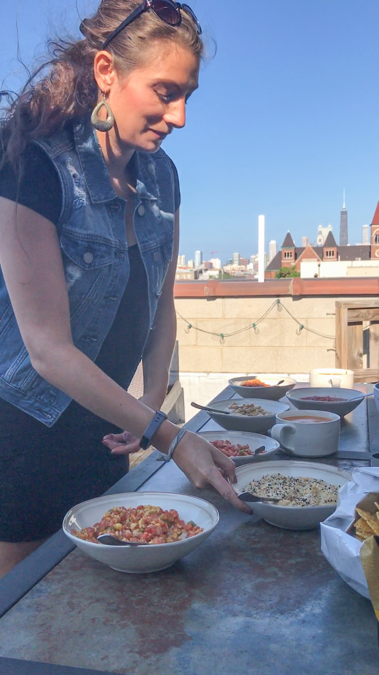 Shalva on our Chicago rooftop serving hummus, salsa, queso and veggies.