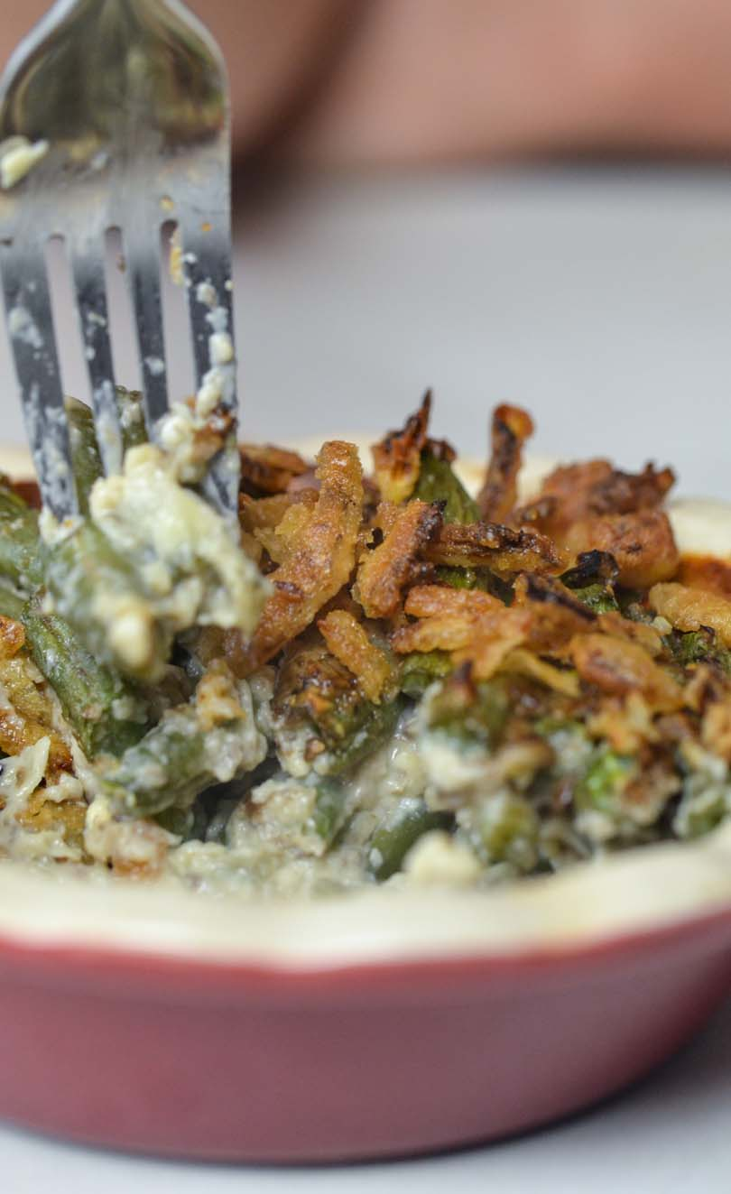 Green bean casserole being tasted with a fork.