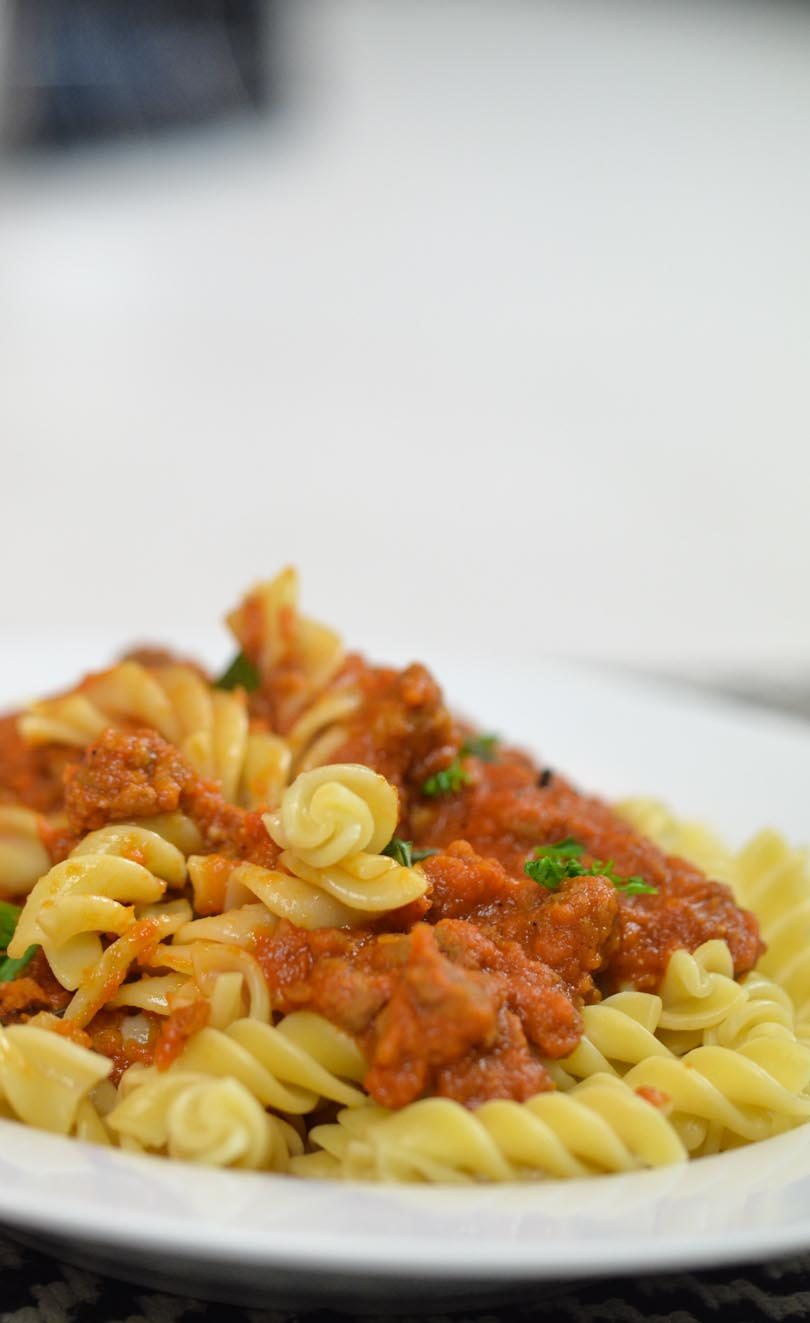 Bolognese sauce mixed into rotini pasta.