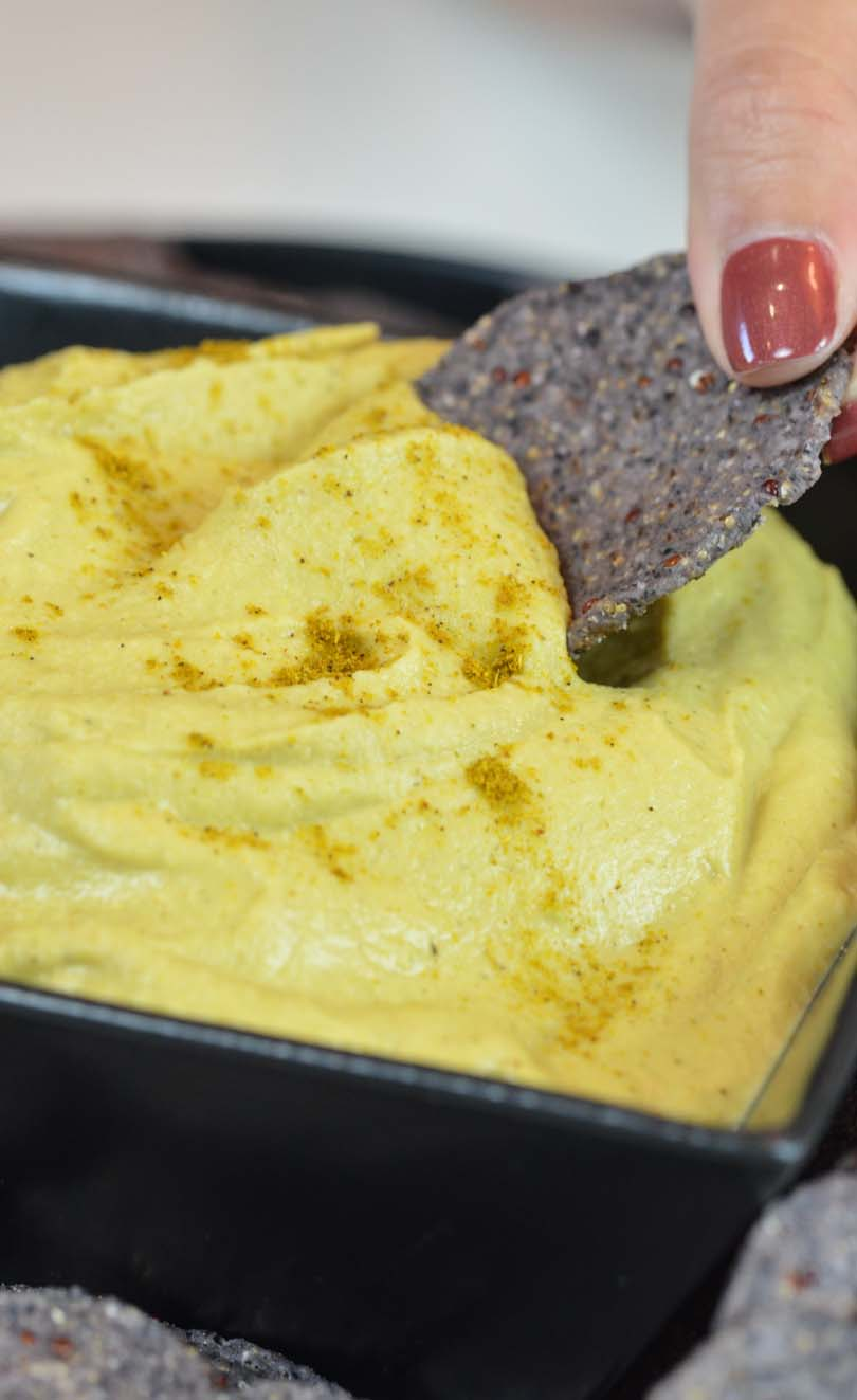 Thai curry hummus getting dipped by a chip.