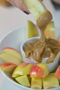 Dipping a slice of apple into caramel dip.