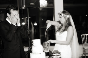 Lenny covering his eyes as Shalva serves a Vitamix'd wedding cake slice.
