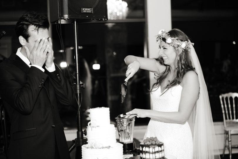 Lenny covering his eyes as Shalva serves a Vitamix'd wedding cake slice.