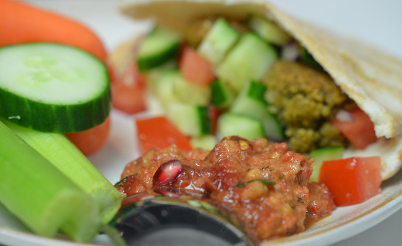 Side of muhammara with falafel sandwich.