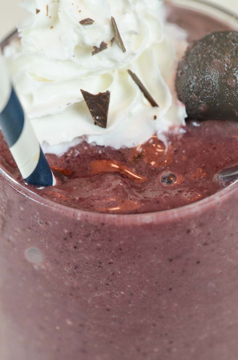 Red velvet shake with whip cream and chocolate shavings.