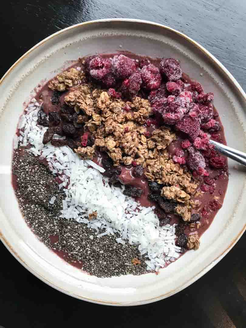 Red velvet shake as a smoothie bowl with granola, fruit and seeds.