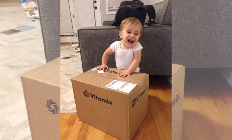Baby with a Certified Reconditioned standard Programs Vitamix in box.