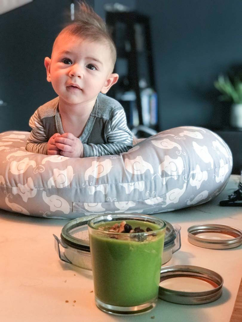 Baby with green juice from a Vitamix.