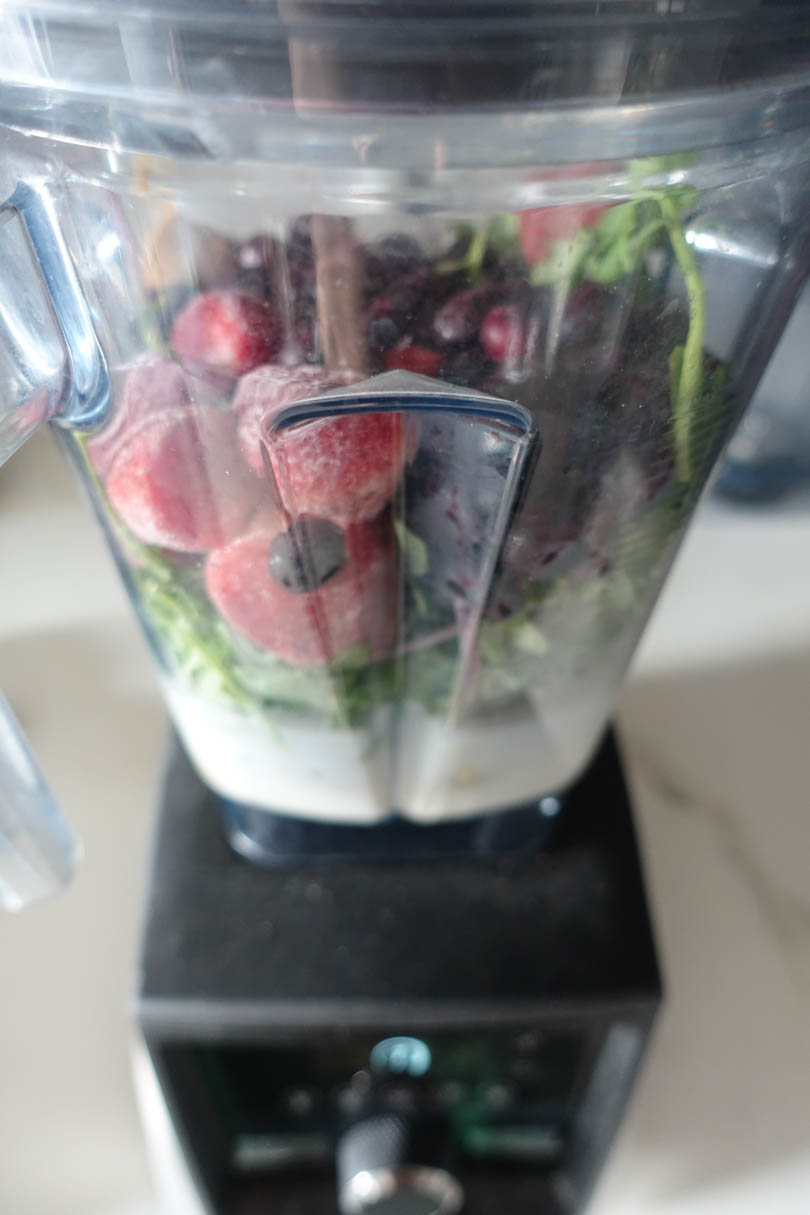 Frozen strawberries blueberries peanut butter and greens in a Vitamix A3500.
