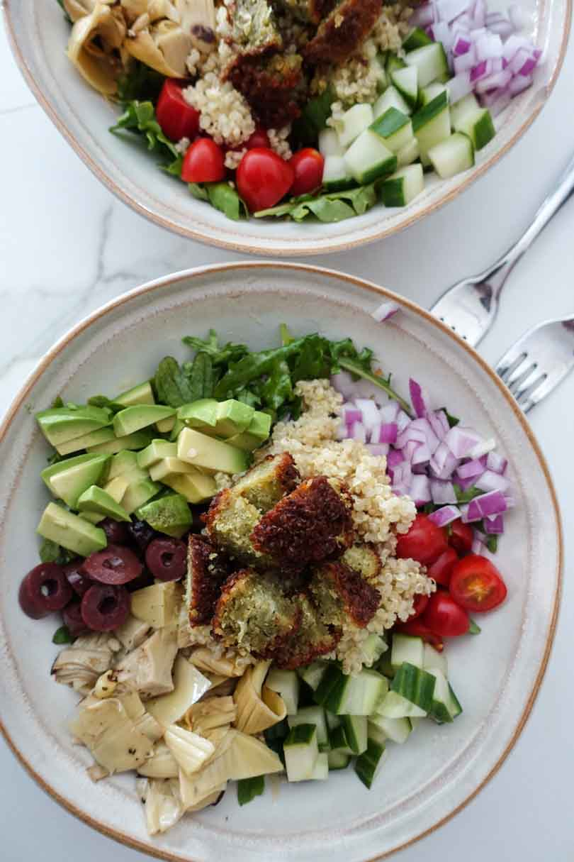 Salad with artichoke cucumber onion tomato quinoa avocado and olives.