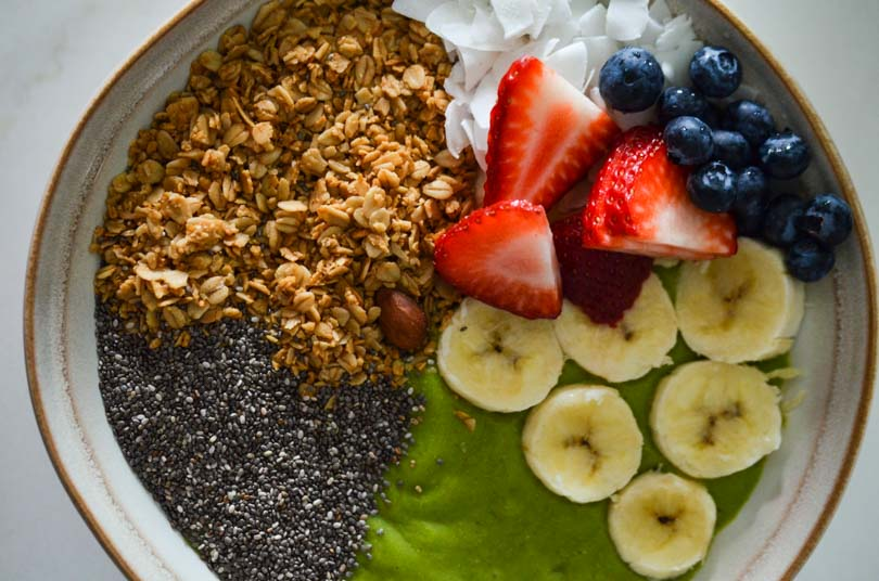 Green smoothie bowl with granola, strawberries, blueberries, banana, and chia seeds.