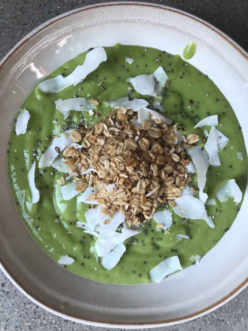 Green smoothie bowl with toppings sprinkled.