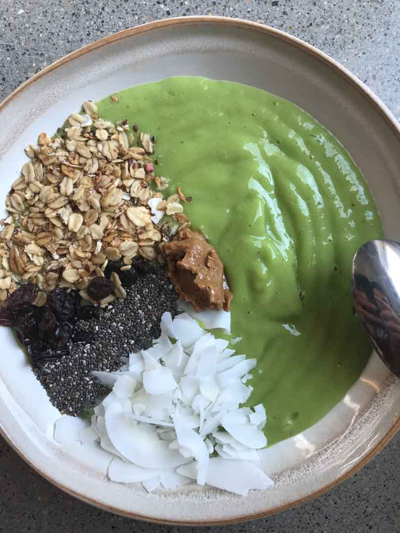 Green smoothie bowl with toppings in sections.
