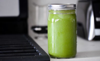 Green juice in a jar in front of a Vitamix A3500