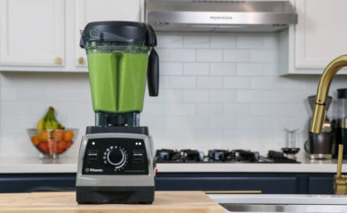 Green juice inside a Pearl Gray Vitamix Pro 750 in a white kitchen.