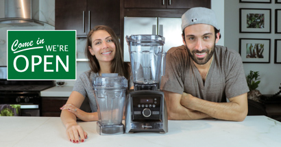 "Shalva and Lenny Gale with Vitamix A3500 and 48 oz container for Life is No Yoke with a ""come we're open"" sign."