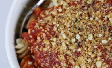 vegan parmesan over pasta with red sauce