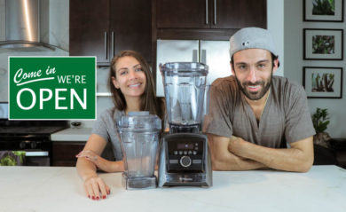 Shalva and Lenny Gale of Life is No Yoke with a Vitamix and we're open sign.