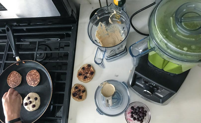 Secondary narrow Vitamix container with low-profile 64-ounce making pancakes and green juice.